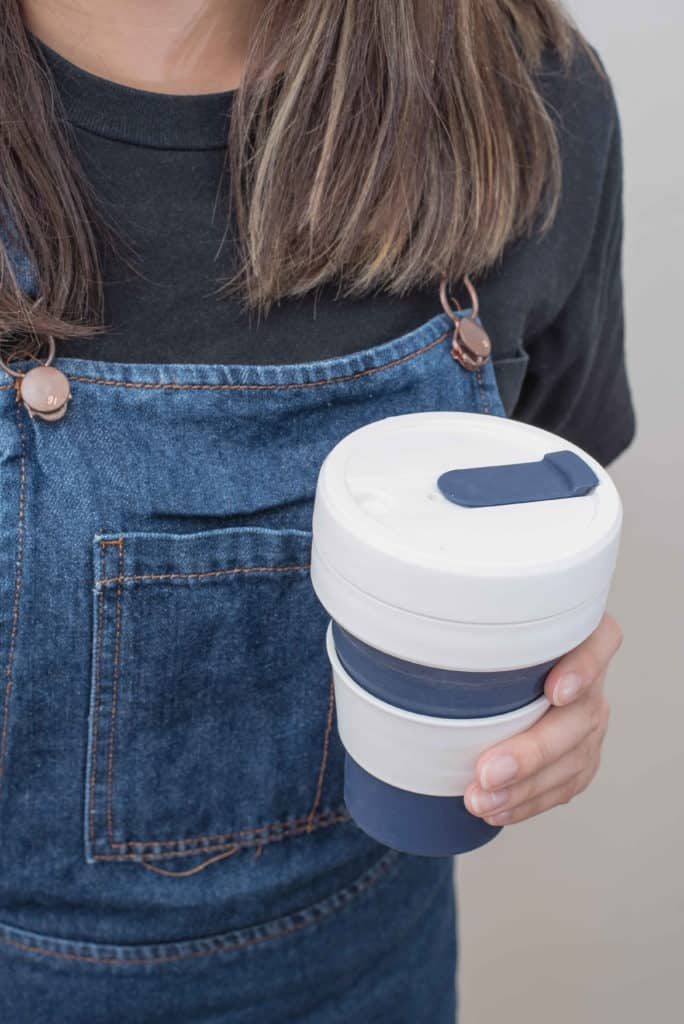 Young woman holding a silicone collapsible cup, reusable coffee tumbler.