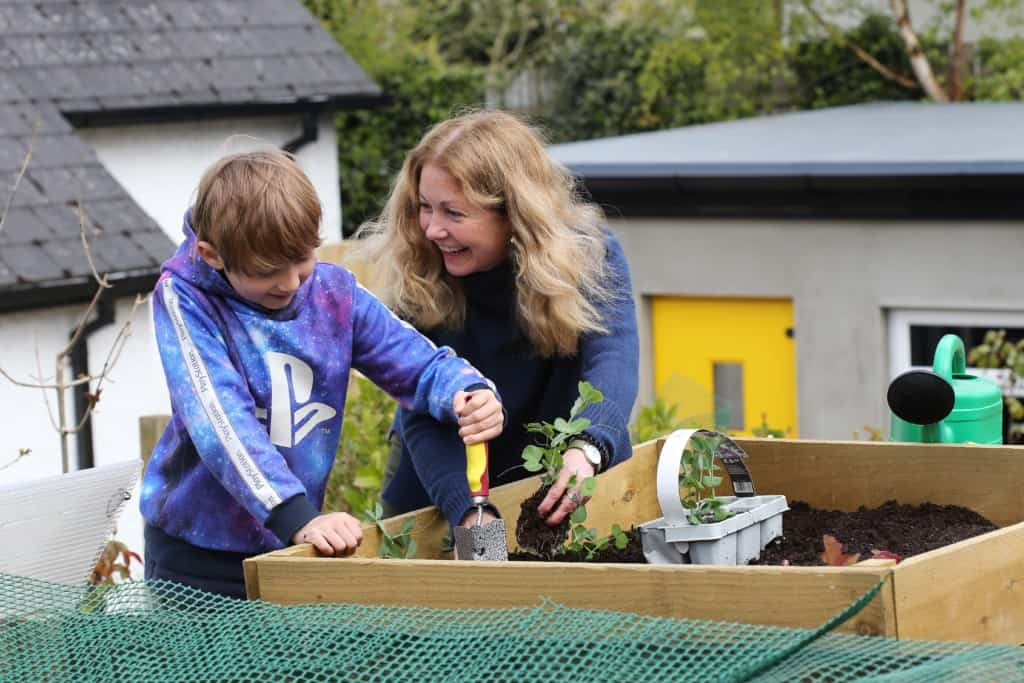 Woman with seedling smiles at boy holding trowel