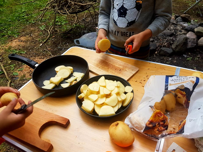 Table with two pans containing chopped up potatoes