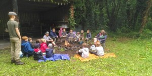 Group of children sitting on grass around a campfire at the edge of a forest,